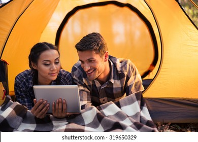 Portrait of a happy couple lying in tent and using tablet computer in forest