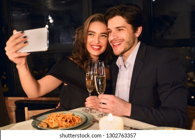 Portrait of happy couple making selfie on smart phone during romantic dinner in restaurant. Capturing happy moments concept