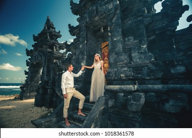 Portrait of happy couple near traditional gate. Traveling at Bali, nusa duo. Honeymoon summer travel at Indonesia.