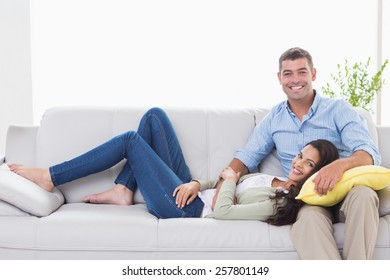 Portrait of happy couple on sofa at home