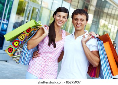 Portrait of happy couple with paperbags after shopping