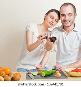 Portrait of a Happy couple preparing food in the kitchen and drinking red wine