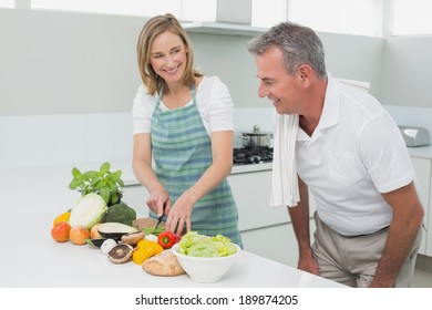 Portrait of a happy couple preparing food together in the kitchen at home