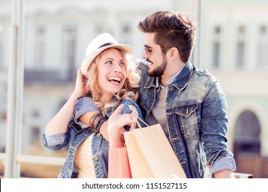 Portrait of happy couple with shopping bags after shopping in city.