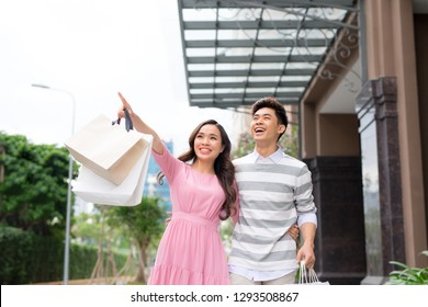 Portrait of happy couple with shopping bags after shopping in city smiling and huging.