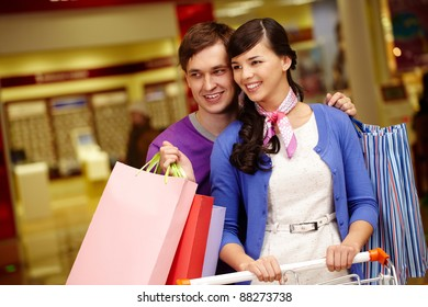 Portrait of happy couple shopping in the mall