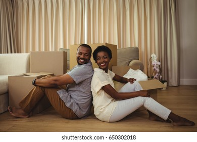 Portrait of happy couple sitting back to back in living room at home