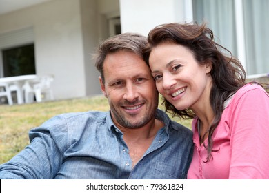 Portrait of happy couple sitting in front of their new house