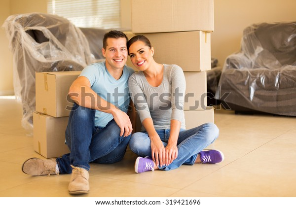 portrait of happy couple sitting in new house