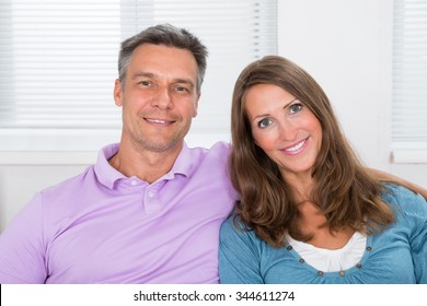 Portrait Of Happy Couple Sitting On Couch In Living Room