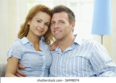 Portrait of happy couple sitting on sofa embracing, looking at camera and smiling.