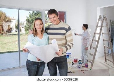 Portrait of happy couple smiling with painter in background