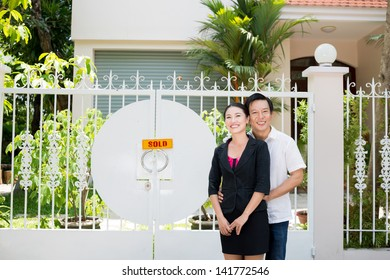 Portrait of a happy couple standing in front of their new house