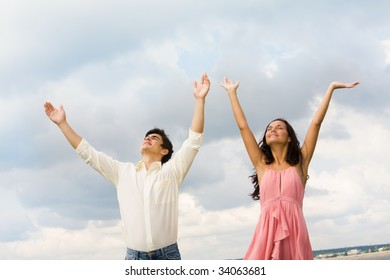 Portrait of happy couple standing with raised arms on background of cloudy sky