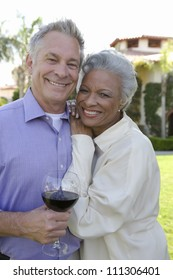 Portrait happy couple standing together while man holding wine glass
