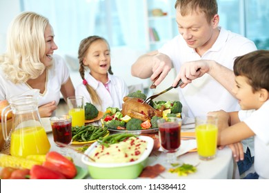 Portrait of happy couple and their children sitting at festive table and going to eat roasted turkey