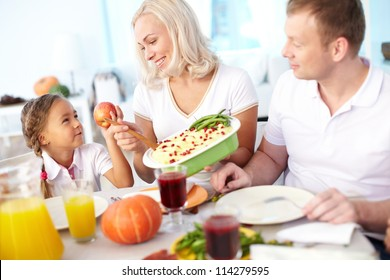 Portrait of happy couple and their daughter sitting at festive table and going to eat mashed potatoes