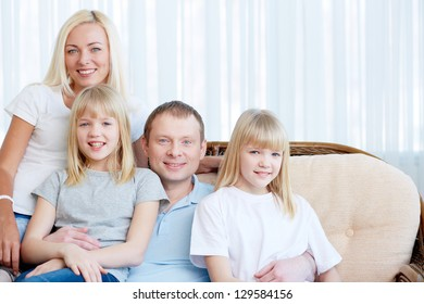 Portrait of happy couple with twin daughters looking at camera with smiles