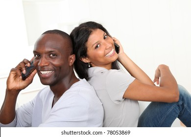 Portrait of happy couple using cellphone