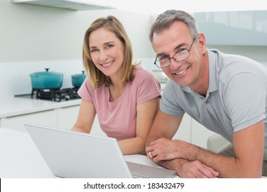Portrait of a happy couple using laptop in the kitchen at home