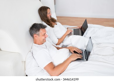 Portrait Of A Happy Couple Using Laptop On Bed