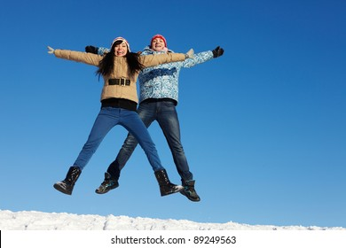 Portrait of happy couple in warm clothes jumping and looking at camera