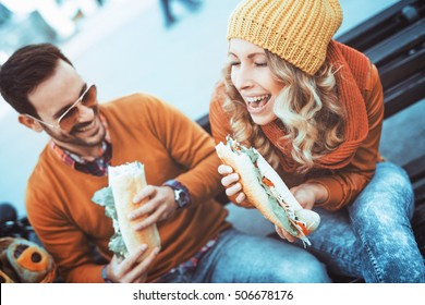 Portrait of an happy couple.They are laughing and eating sandwich and having a great time.