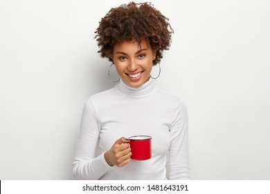 Portrait of happy curly haired woman with toothy smile, holds red mug of hot drink, looks straightly at camera, being coffee lover, dressed in white turtleneck jumper, has spare time, break after work