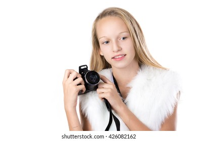 Portrait of happy cute beautiful blond girl wearing white furry outfit, holding digital camera with thoughtful expression, looking for shot, isolated studio image, white background, copy space