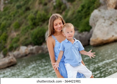 Portrait of happy cute big sister and little brother near beach. Italy outdoor