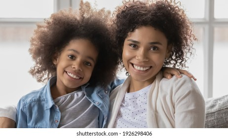 Portrait of happy cute Black mom and kid looking at camera and smiling. Mother and daughter girl relaxing on couch at home, enjoying leisure time together. Family, parenting concept. Close up