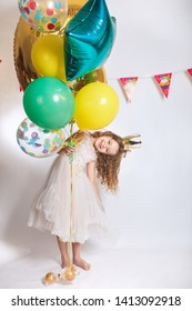 Portrait of a happy cute girl with balloons on birthday party