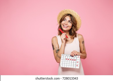 Portrait of a happy cute girl in summer hat holding her periods calendar with a felt-tip pen and looking away at copy space isolated over pink background