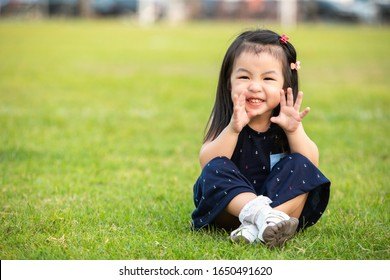 Portrait of happy cute little Asian girl child with bawl outdoors in summer day