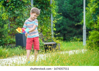Portrait of a happy cute little boy holding pinwheel at the park. kid hold in hand play with windmill. boy smiling in spring or summer forest. Outdoors leisure weekend family concept.
