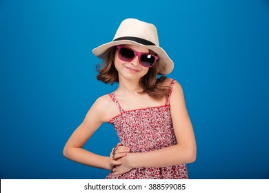 Portrait of happy cute little girl in hat and sunglasses posing over blue backgound