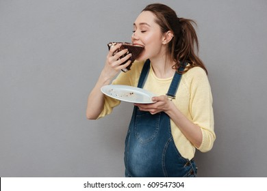 Portrait of a happy cute pregnant woman biting chocolate cake isolated on a gray background