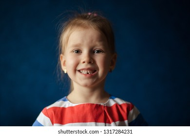 portrait of happy cute toothless blonde girl 3-4 years old on blue background