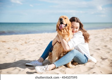 Portrait of happy cute young woman sitting and hugging her dog on the beach