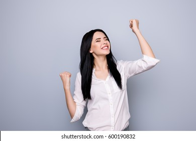 Portrait of happy cute young  woman with toothy smile raised hands  and celebrate achievement goal.