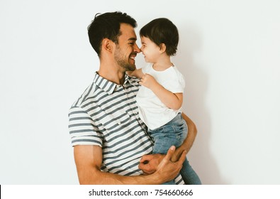 Portrait of happy dad and daughter play and cuddle together against white background. Good relationship of parent and child. Happy family moments of father and toddler girl. Childhood and parenthood.