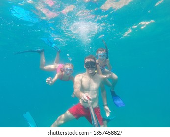 Portrait of a happy dad with two little daughters under water in sea