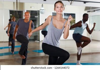 Portrait of happy dancing people practicing vigorous swing in dance studio