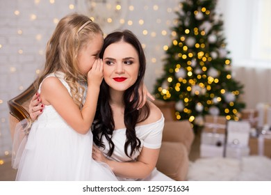 portrait of happy daughter whispering secret or christmas gift wishes to her mother in decorated living room with christmas tree