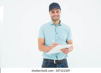 Portrait of happy delivery man writing on clipboard against white background