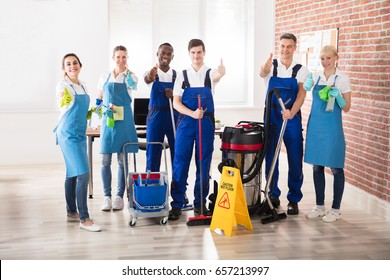 Portrait Of Happy Diverse Janitors In The Office With Cleaning Equipments Showing Thumb Up Sign