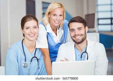 Portrait of happy doctor team at desk in hospital