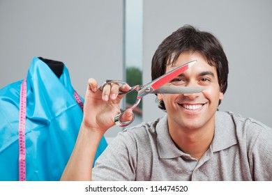 Portrait of happy dressmaker holding scissor with mannequin in background