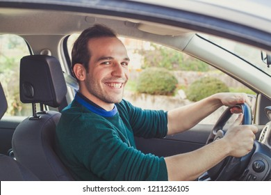Portrait of happy driver in car. Smiling young man looking at camera who got his driving license.
