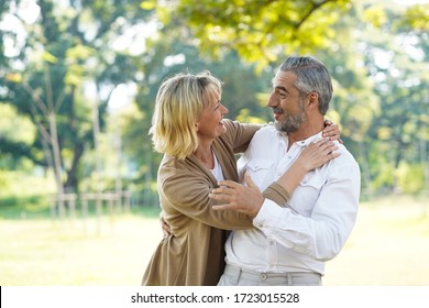 Portrait of happy elder couple hug and take care together with good relationship and good health in the park. Retirement and lovely couple concept.